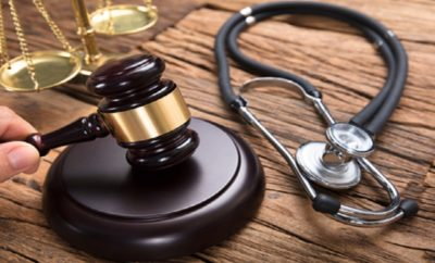 83075255 - judge hitting mallet by stethoscope and justice scale on wooden table in courtroom
